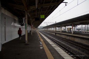 Narita station platform, with one lone person, in the rain