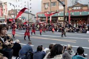 parade members in various forms of armor, led by a samurai in full battle gear