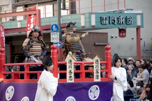 two men on float in Japanese armor, waving to the crowd